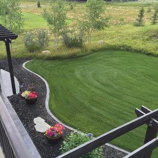 Exemple d'une grande terrasse arrière avec des solutions pour vis-à-vis et une pergola.