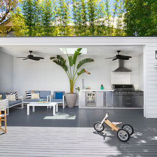 This is an example of a contemporary backyard deck in Sydney with an outdoor kitchen and a pergola.