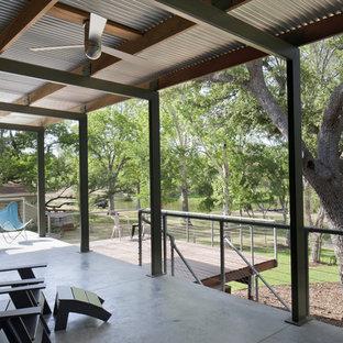 Cette photo montre une terrasse moderne avec une extension de toiture.