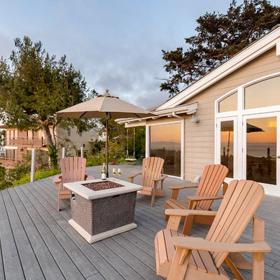 Huge beach style backyard deck photo in Los Angeles with a fire pit and no cover