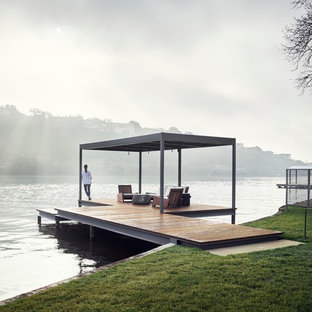 Photo of a small contemporary backyard deck in Austin with with dock.