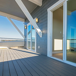 Large transitional backyard deck photo in Seattle with a roof extension