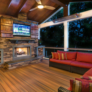 Inspiration for a rustic deck remodel in Charlotte with a fire pit and a roof extension