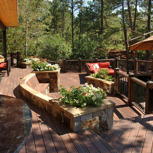 Large southwest outdoor kitchen deck photo in Charlotte with a roof extension
