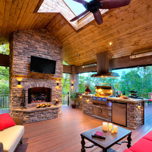 Large elegant backyard outdoor kitchen deck photo in Los Angeles with a pergola