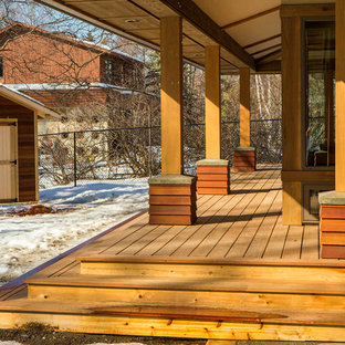 This is an example of a mid-sized arts and crafts backyard deck in Other with a roof extension.