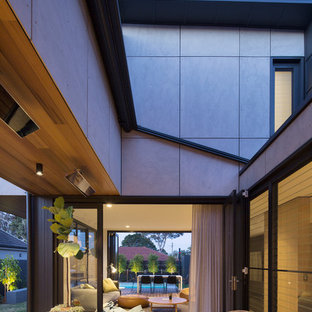 This is an example of a mid-sized contemporary side yard deck in Sydney with an awning.