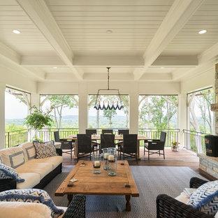 Réalisation d'une grande terrasse arrière tradition avec un foyer extérieur et une extension de toiture.