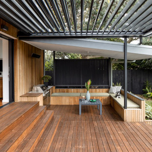 Mid-sized contemporary backyard and ground level deck in Sydney with a pergola.