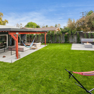 Large transitional backyard deck in Los Angeles with an outdoor shower and a roof extension.