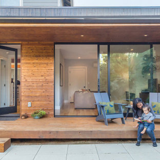 Inspiration for a small modern backyard deck in Portland with with privacy feature and a roof extension.