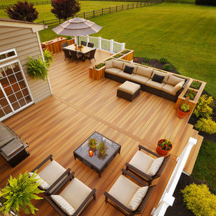 Example of a large transitional backyard outdoor kitchen deck design in Other with no cover