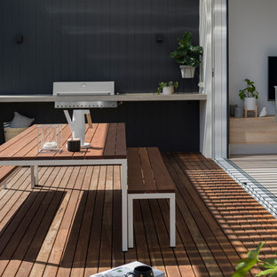 Example of a small danish backyard outdoor kitchen deck design in Adelaide with a pergola
