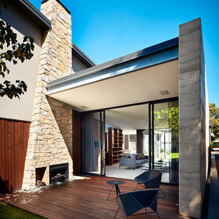 Contemporary backyard deck in Melbourne with a fire feature and a roof extension.