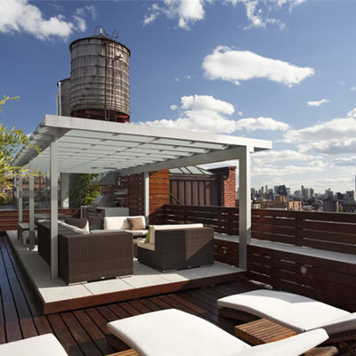 Example of a large minimalist rooftop outdoor kitchen deck design in New York with a pergola