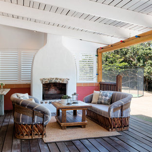 Design ideas for a mediterranean deck in Brisbane with a fire feature and a roof extension.