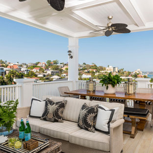 Design ideas for a beach style deck in Brisbane with a roof extension.