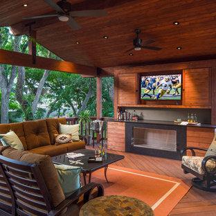 Esempio di una terrazza minimal di medie dimensioni e dietro casa con un focolare e un tetto a sbalzo
