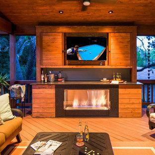 Ispirazione per una terrazza contemporanea di medie dimensioni e dietro casa con un focolare e un tetto a sbalzo