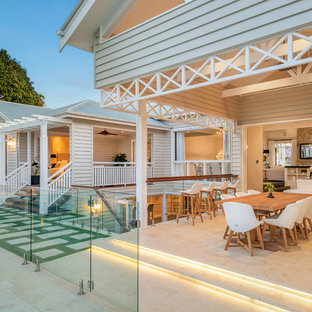 Large retro back terrace and balcony in Brisbane with a roof extension.
