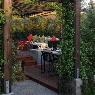 Ispirazione per una terrazza design dietro casa con un focolare e una pergola