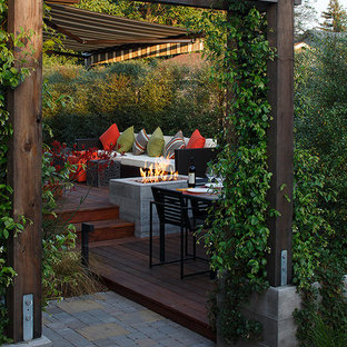 Example of a trendy backyard deck design in San Francisco with a fire pit and a pergola