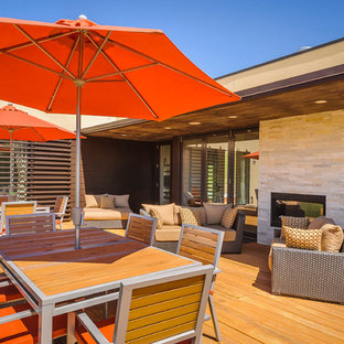 Inspiration for a contemporary backyard deck remodel in San Francisco with a fire pit and a roof extension
