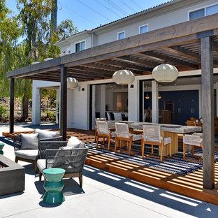 Свежая идея для дизайна: пергола на террасе на заднем дворе в современном стиле с местом для костра - отличное фото интерьера