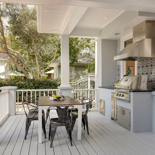 Inspiration for a large transitional backyard outdoor kitchen deck remodel in Tampa with a roof extension