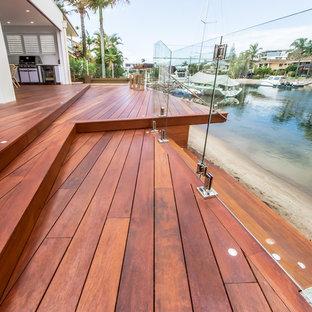 Idee per grandi terrazze e balconi design dietro casa con un pontile e un tetto a sbalzo