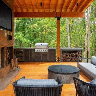 Large mountain style side yard outdoor kitchen deck photo in Other with a roof extension