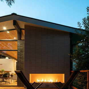 Example of a large mid-century modern backyard deck design in Dallas with a fireplace and no cover