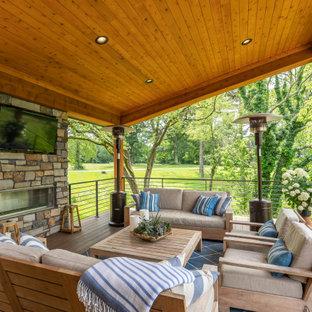 Ispirazione per una terrazza rustica con un caminetto e un tetto a sbalzo