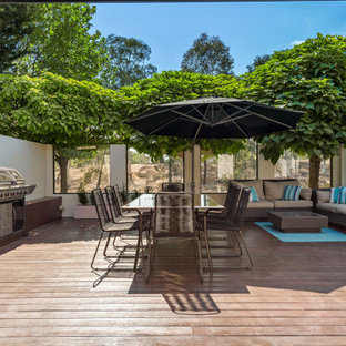 Large contemporary deck in Canberra - Queanbeyan with an outdoor kitchen.
