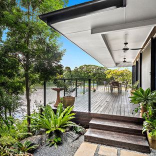 Inspiration for a small beach style backyard deck in Other with a roof extension.