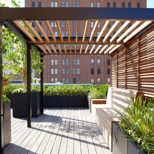 Example of a large trendy rooftop deck container garden design in New York with a pergola