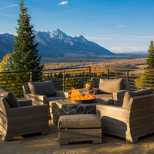 Inspiration for a large rustic backyard deck remodel in Other with a fire pit and no cover