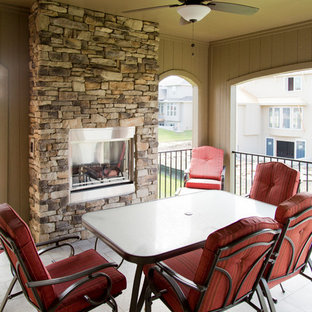 Large farmhouse backyard deck photo in Kansas City with a fireplace and a roof extension