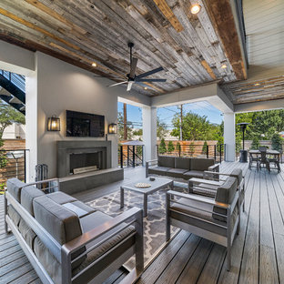 Transitional backyard deck photo in Houston with a fireplace and a roof extension