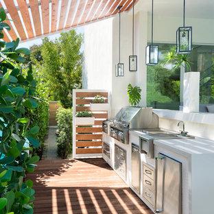 Modelo de terraza marinera, de tamaño medio, con cocina exterior y pérgola