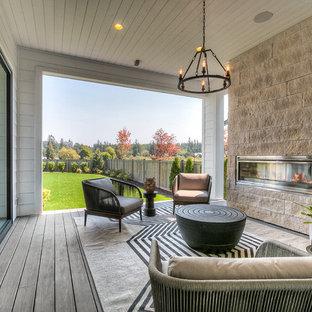 Imagen de terraza clásica renovada, en anexo de casas, con chimenea