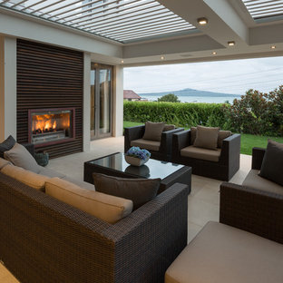 Large trendy backyard deck photo in Auckland with a fire pit and a roof extension