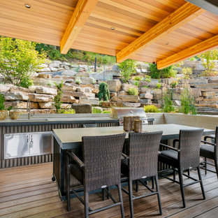 Inspiration for a large contemporary backyard outdoor kitchen deck remodel in Seattle with a roof extension