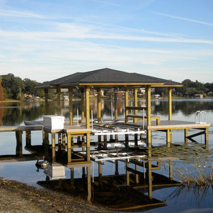 This is an example of a mid-sized beach style backyard deck in Orlando with with dock.