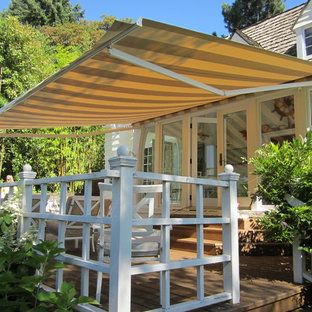 Design ideas for a mid-sized traditional backyard deck in Portland with with dock and an awning.
