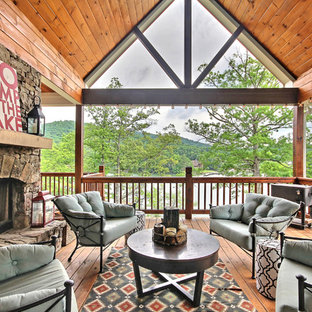 Inspiration for a rustic backyard deck remodel in Atlanta with a fire pit and a roof extension