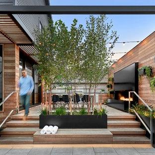 Esempio di una terrazza contemporanea nel cortile laterale con un caminetto e nessuna copertura