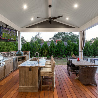 Inspiration for a large timeless backyard outdoor kitchen deck remodel in Other with a roof extension