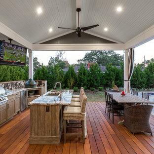 Ispirazione per una grande terrazza tradizionale dietro casa con un tetto a sbalzo