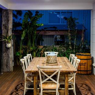 Foto di una terrazza tropicale dietro casa con un tetto a sbalzo